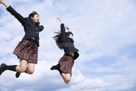 青空をバックにジャンプをする女子高校生たちの写真素材 [FYI02969983]
