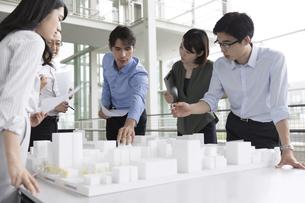 建築模型を使って打ち合せをするビジネス男女の写真素材 [FYI02969996]
