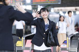 駅の改札付近で友達に手を振る女子高校生の写真素材 [FYI02970004]
