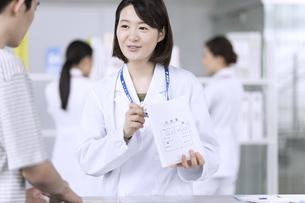 受付で薬の説明をする女性薬剤師の写真素材 [FYI02970013]