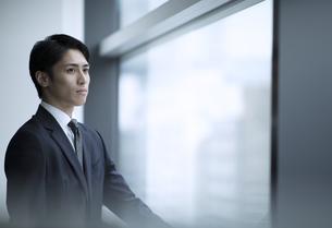 窓から遠くを見るビジネス男性の写真素材 [FYI02970017]