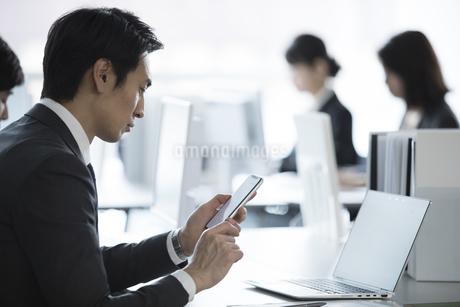 スマートフォンを見るビジネス男性の写真素材 [FYI02970024]