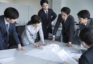 製図と模型を使って打ち合わせをするビジネスマンの写真素材 [FYI02970028]