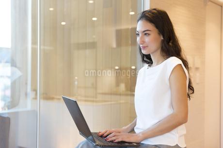 パソコンを開き遠くを見る女性の写真素材 [FYI02970029]