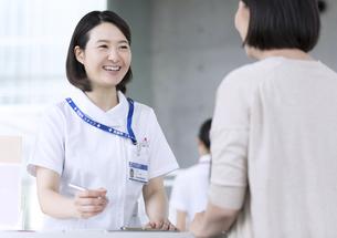 受付で対応を行う女性看護師の写真素材 [FYI02970035]
