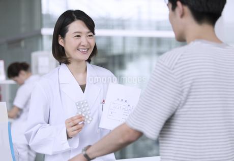 受付で薬の説明をする女性薬剤師の写真素材 [FYI02970036]