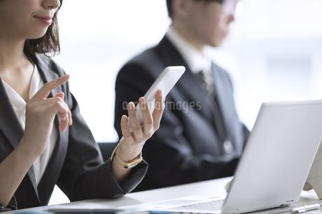 スマートフォンを操作するビジネス女性の手元の写真素材 [FYI02970041]