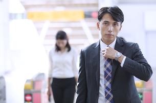 駅の改札付近でネクタイを締め直すビジネス男性の写真素材 [FYI02970042]