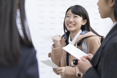 受験番号票を手に合格を喜ぶ女子高校生の写真素材 [FYI02970044]