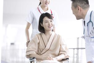 車椅子の患者に添う男性医師と女性看護師の写真素材 [FYI02970055]