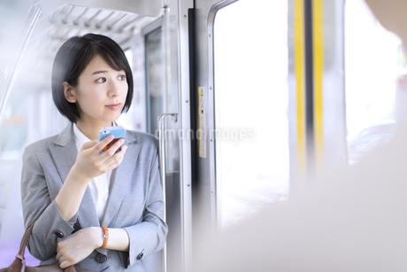 電車で外の景色を見つめるビジネス女性の写真素材 [FYI02970058]