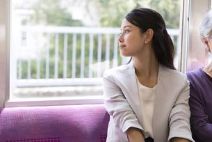 電車で外の景色を見つめるビジネス女性の写真素材 [FYI02970059]