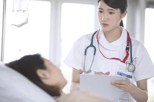 入院患者から話しを聞く女性看護師の写真素材 [FYI02970062]