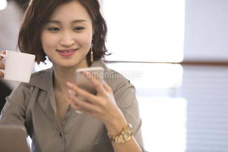 スマートフォンを見るビジネス女性の写真素材 [FYI02970068]