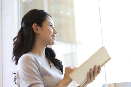 本を持ち遠くを見つめる女性の写真素材 [FYI02970069]