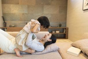 ソファーで戯れる母親と娘の写真素材 [FYI02970075]