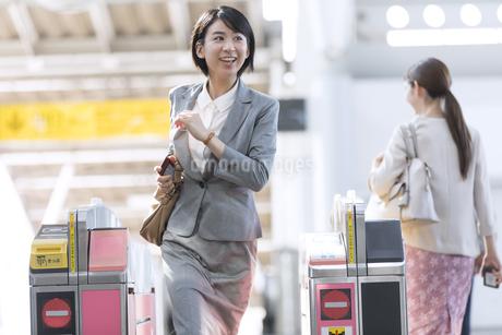 駅の改札を走って通過するビジネス女性の写真素材 [FYI02970076]