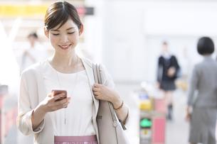 駅の改札付近でスマホを見るビジネス女性の写真素材 [FYI02970078]