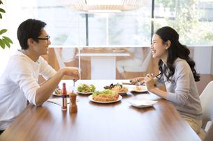 ダイニングテーブルで食事を楽しむ夫婦の写真素材 [FYI02970081]