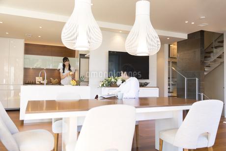 夫と会話をしながら料理をする妻の写真素材 [FYI02970088]