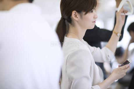 電車で外の景色を見つめるビジネス女性の写真素材 [FYI02970092]