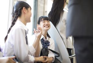 電車で友人と会話をする女子高校生たちの写真素材 [FYI02970093]