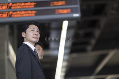 駅のホームで遠くを見る男性の写真素材 [FYI02970096]
