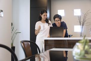 キッチンでパソコンを見る夫婦の写真素材 [FYI02970098]