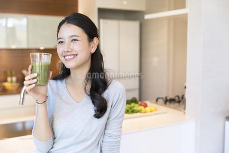 スムージーを手に微笑む女性の写真素材 [FYI02970104]