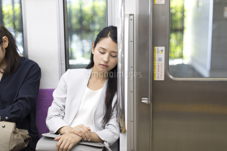 電車の座席に座り眠るビジネス女性の写真素材 [FYI02970105]