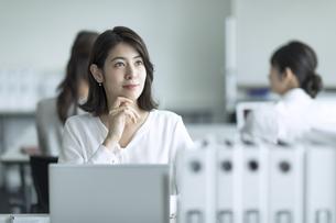 パソコンの前で遠くを見るビジネス女性の写真素材 [FYI02970106]