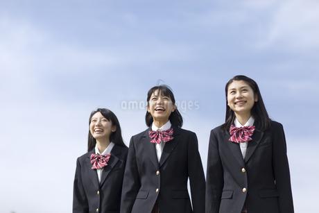 青空をバックに立つ女子高校生たちの写真素材 [FYI02970115]