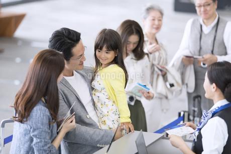 空港カウンターで手続きをする家族の写真素材 [FYI02970125]