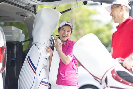 車からゴルフバッグを取り出す夫婦の写真素材 [FYI02970126]