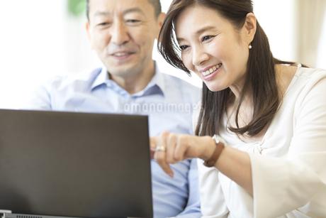 パソコンを見ながら会話をする夫婦の写真素材 [FYI02970127]