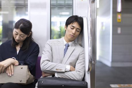 電車で眠るビジネス男性の写真素材 [FYI02970132]