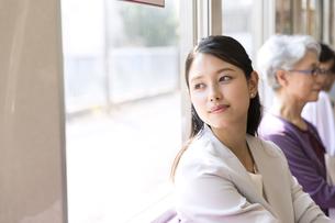 電車で外の景色を見つめるビジネス女性の写真素材 [FYI02970134]