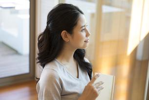 本を持ち遠くを見つめる女性の写真素材 [FYI02970139]