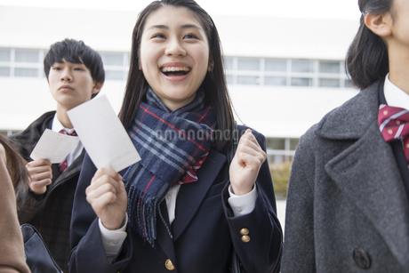 受験番号票を手に合格を喜ぶ女子高校生の写真素材 [FYI02970142]