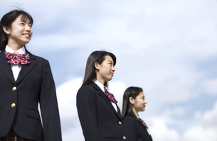 青空をバックに立つ女子高校生たちの写真素材 [FYI02970143]
