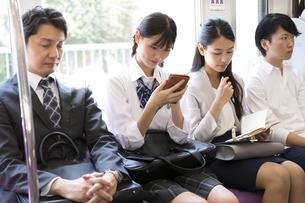 電車でスマホを操作する女子高校生の写真素材 [FYI02970149]