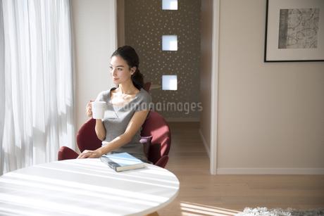 椅子に座りカップを持つ女性の写真素材 [FYI02970150]
