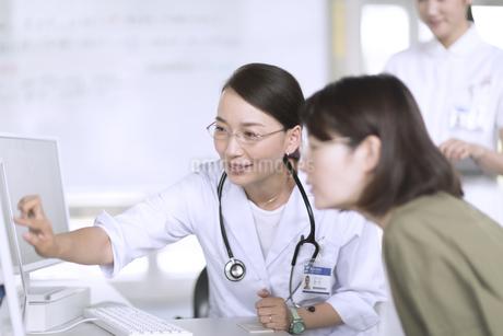モニターを使って患者に説明をする女性医師の写真素材 [FYI02970152]