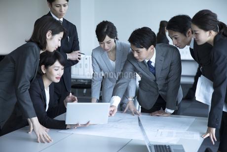 製図を広げて打ち合わせをするビジネスマンの写真素材 [FYI02970153]
