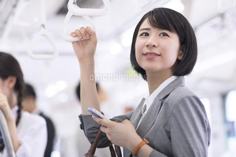 電車でつり革を持ち遠くを見つめるビジネス女性の写真素材 [FYI02970154]