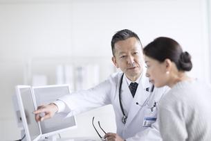 モニターを使って患者に説明をする男性医師の写真素材 [FYI02970160]