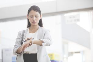 駅で時計を見るビジネス女性の写真素材 [FYI02970163]