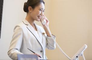電話対応をするコンシェルジュの女性の写真素材 [FYI02970166]