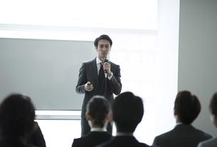 マイクを手に講義をするビジネス男性の写真素材 [FYI02970169]
