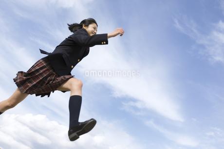 青空をバックにジャンプをする女子高校生の写真素材 [FYI02970170]